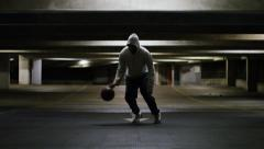 Hooded male basketball player practicing his dribbling skill at night Stock Footage