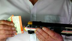 Man holding model train and tickets. Stock Footage