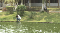 Chinese student reflecting by pond, China - stock footage