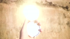 Female Hand Moves a Small Mirror Making Sunbeams. Slow Motion Stock Footage