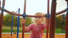 Adorable little girl starts climbing the jungle gym - stock footage