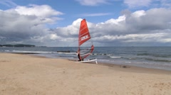 Person detaches sail from the windsurfing board in Sopot, Poland. Stock Footage