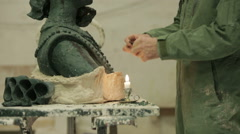 A sculptor using a candle to heat wax as he sculps a head to be cast in bronze Stock Footage