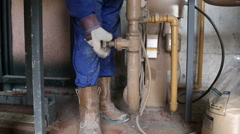 A worker regulating the gas flow into a furnace melting bronze Stock Footage