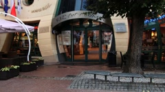 People walk in front of the Crooked house in Sopot, Poland. Stock Footage