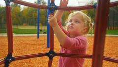 Beautiful little girl plays on jungle gym - stock footage