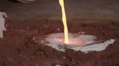 Workers in a bronze foundry pouring bronze into investments for a bronze statue Stock Footage