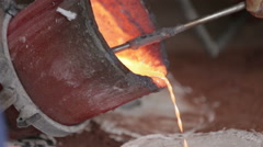 Workers in a bronze foundry pouring bronze into investments for a bronze statue - stock footage