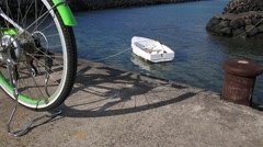 A white small boat floating on the sea and a green bicycle on the embankment Stock Footage