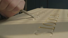 A stone mason carving lettering on a stone plinth in a workshop Stock Footage