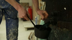 Bronze foundry worker pouring melted wax into a pot Stock Footage