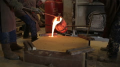 Workers in a bronze foundry pouring bronze into investments for a bronze satue Stock Footage