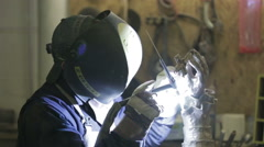 Man in bronze foundry welding bronze to piece together parts of a statue - stock footage