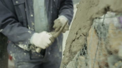 A sculptor in a workshop adding clay to a wire amature Stock Footage