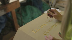 A female using a paint bursh to apply gold leaf to a stone plinth - stock footage