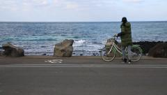 Asian woman in winter clothes riding a bicycle and pulling it over by the ocean Stock Footage