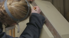 A female stone mason measuring the angle of a stone to be used as a plinth Stock Footage