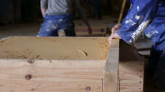Man in a workshop using a piece of wood to flatten sand in a wooden structure Stock Footage