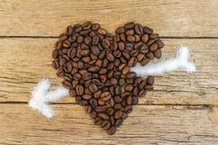 Coffee beans heart stabbed by white sugar on wooden background - stock photo