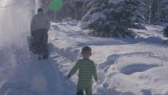 Little boy watching daddy use the snowblower Stock Footage