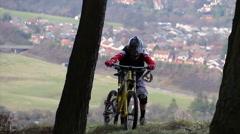 Man pushing DH mountain bike up hill through trees Stock Footage