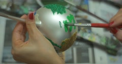 Female Hands Are Painting a Silver Christmas Ball with Green Paint by Brush Stock Footage