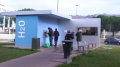 People pour free water from a specially equipped source Stock Footage