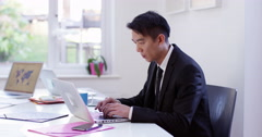 Tired and stressed Asian businessman at work. Shot on RED Epic. Stock Footage