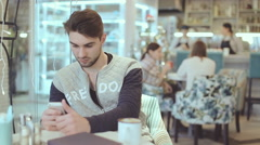 Young man with smartphone sitting in cafe Stock Footage
