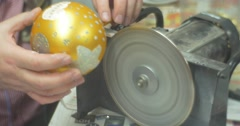 Cap Into a Golden Ball Man is Sawing Out a Glass Handle of a Christmas Toy Ball Stock Footage