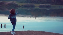 Girl throwing rocks in the lake. Shot in slow motion Stock Footage