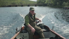 Man going fishing in small boat Stock Footage
