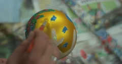 Mother's Hand is Putting a Glue to Christmas Ball to Put a Glitter Childish - stock footage