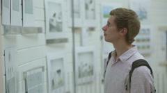 Man looking at an art display through glass Stock Footage