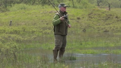 A fisherman casting is fly fishing rod in a loch in Scotland on a sunny day Stock Footage