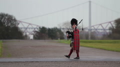 A scottish piper playing the bagpipes in traditional tartan outfit Stock Footage