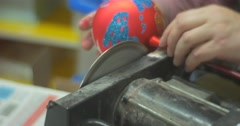 Man is Sawing Out a Glass Handle of a Ball Red Christmas Toy before Give the Stock Footage