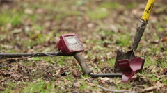 Metal detector and spade propped up in field ready for use - stock footage