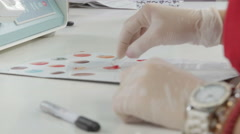 Lab technician determining blood types, hands and cuvette close up, blood sample - stock footage