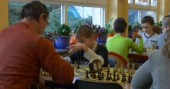 A Preschool Boy Playing Chess With an Adult Man, Waving His Hands, Smiling, and Stock Footage