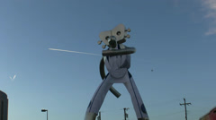 Traveling Man Metal Sculpture With Jet Contrails In Sky Stock Footage