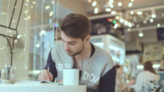 Young man writing in notepad in cafe Stock Footage