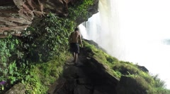 A view behid a raging and roaming waterfall - stock footage