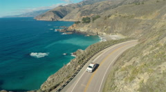 Aerial drone view of car driving down coast country road in Big Sur, California Stock Footage