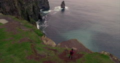 Man walking along the Cliffs of Moher Stock Footage