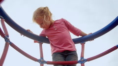 Little girl hangs out on top of the jungle gym - stock footage
