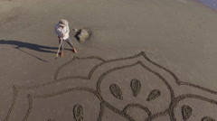 Man drawing a flower mandala design on the beach Stock Footage