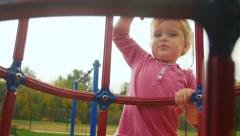 Girl looks at camera and climbs jungle gym - stock footage