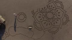 Man drawing a flower mandala design on the beach - stock footage