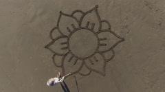 Man drawing a flower mandala on the beach Stock Footage